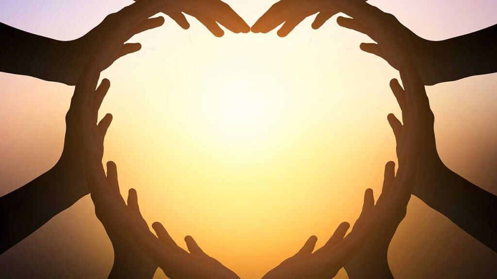 multiple hands forming a heart in unity