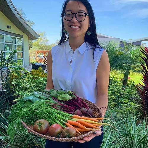woman holding veggies from garden